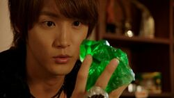 Haruto holding a green magic stone